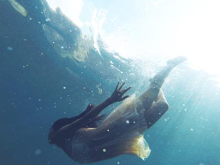 Onderwater foto van een mens duiken in blauwe zeewater