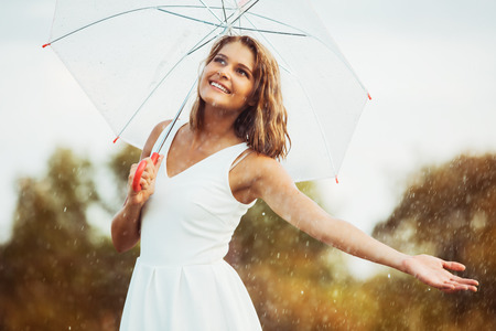 Portrait of beautiful young girl walking with umbrella under rain photo