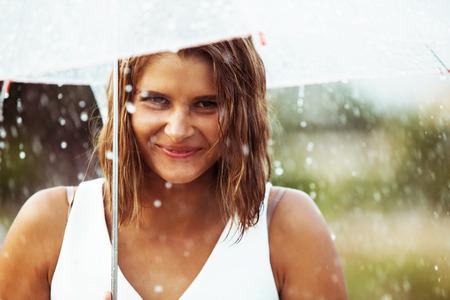 雨の中傘を持って歩く美しい若い女の子の肖像画 写真素材