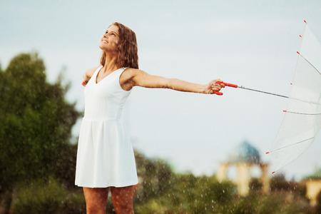 bad feeling: Portrait of beautiful young girl walking with umbrella under rain