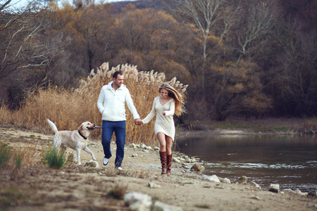 Young happy couple walking with dog near the lake in autumn photo