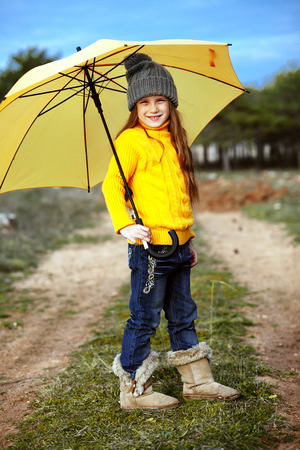 yellow umbrella: Cute 7 years old girls wearing knitted winter sweaters walking outdoors in autumn Stock Photo