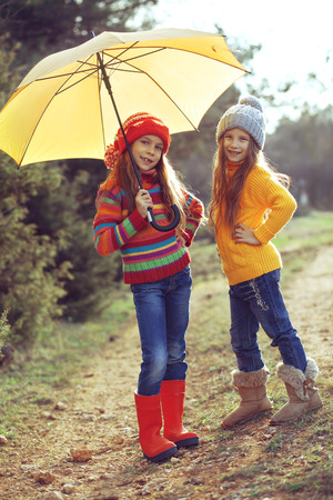 Cute 7 years old girls wearing knitted winter sweaters walking outdoors in autumn photo