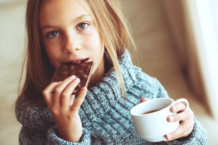 Kind tragen Pullover und Tee trinken zu Hause Standard-Bild