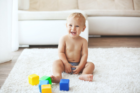1 year old: Toddler playing with toys on a white carpet at home Stock Photo