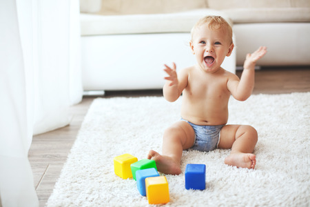 one year old: Toddler playing with toys on a white carpet at home Stock Photo