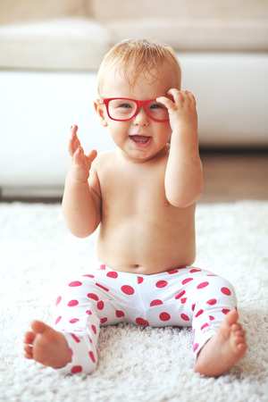 1 year old: Toddler playing with glasses on a white carpet at home Stock Photo