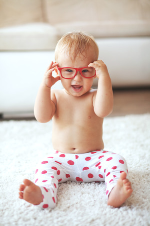 Toddler playing with glasses on a white carpet at home Stock Photo