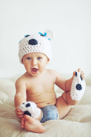 Portrait of a cute 1 year old baby dressed in a bear hat photo