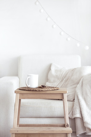 Detalles interiores Naturaleza muerta, taza de café y un libro cerca acogedora silla blanca