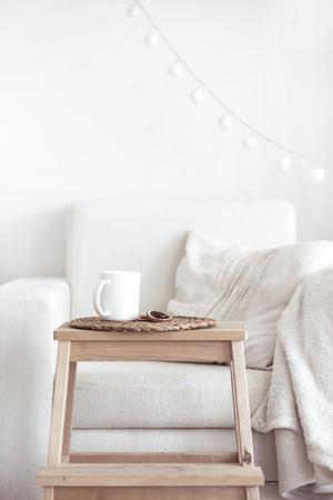 Stilleven interieur, een kop koffie en een boek in de buurt van witte gezellige stoel Stockfoto