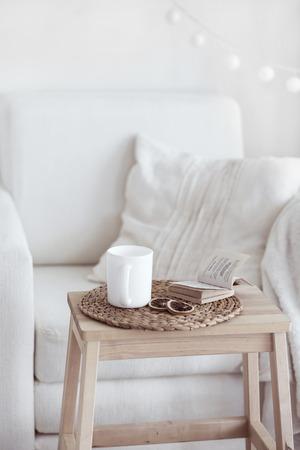 여전히 삶의 인테리어 세부 사항, 커피 한잔과 흰색 아늑한 의자에 가까운 책