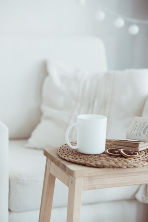 Still life interior details, cup of coffee and a book near white cozy chair Foto de archivo