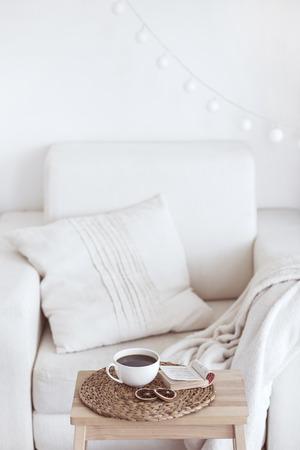 Stilleven interieurdetails, een kop koffie en een boek in de buurt van witte gezellige stoel