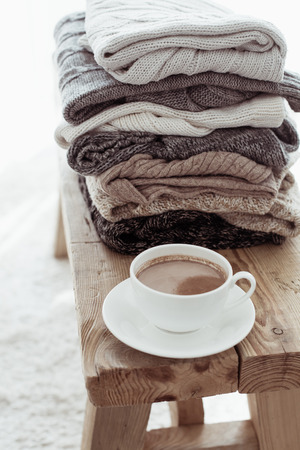 scandinavian: Still life details, stack of winter sweaters on rustic bench on white carpet