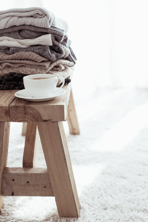 details: Still life details, stack of woolen sweaters on rustic bench on white carpet