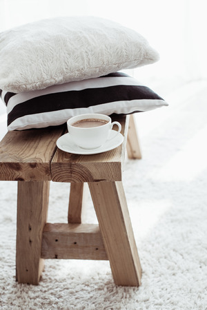 Still life details, stack of black and white cushions on rustic bench on white carpet photo