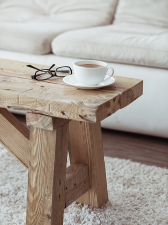 Still life details, cup of coffee on rustic bench over white sofa