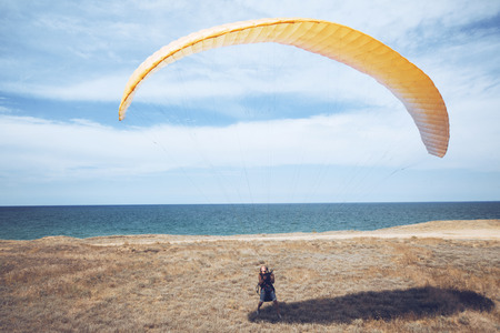 risk taking: Paraglider taking off from a hill near sea