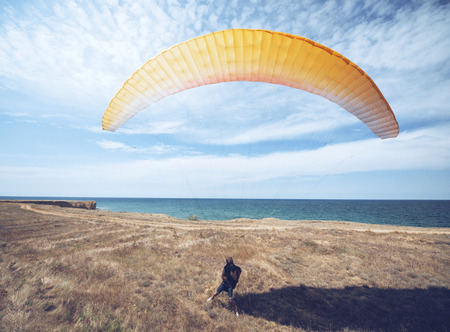 skydive: Paraglider taking off from a hill near sea