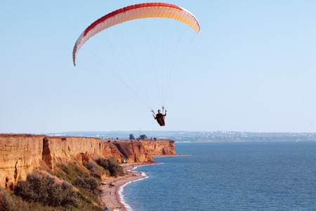 taking risks: Paraglider flying in the sky under the sea coastline Stock Photo