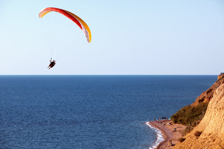 skydive: Paraglider flying in the sky under the sea coastline Stock Photo