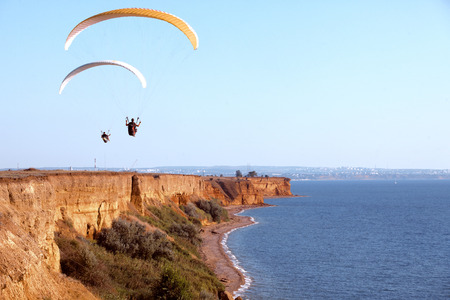 risk taking: Paraglider flying in the sky under the sea coastline Stock Photo