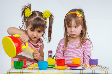 age 5: Two 5 years old kids playing with plastic tableware toys
