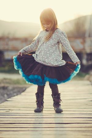 Cute 5 years old girl wearing tutu skirt posing over sunset sunlight in rustic scene