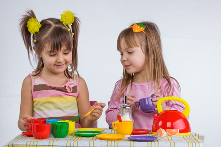 2 years old: Two 5 years old kids playing with plastic tableware toys