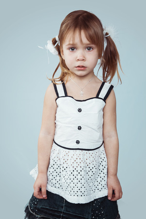 Portrait of sad little girl, studio shot photo