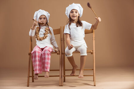 Two 5 years old girls bakers studio shot photo