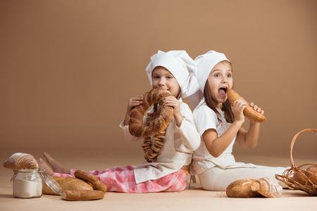 Two 5 years old girl bakers eating bakery products, studio shot photo
