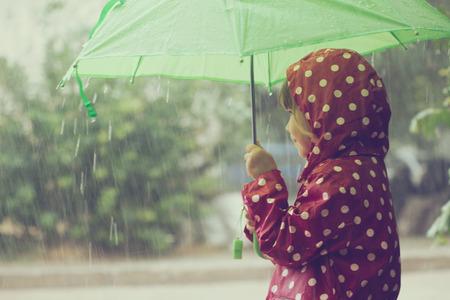 lluvia paraguas: Niño poco caminar bajo la lluvia