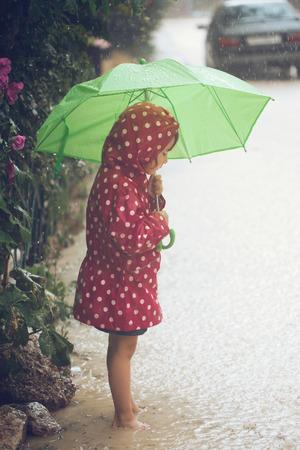 umbrella rain: Little child walking in the rain