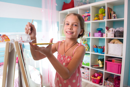 eight year old: 7-8 years old child drawing on easel in child room at home
