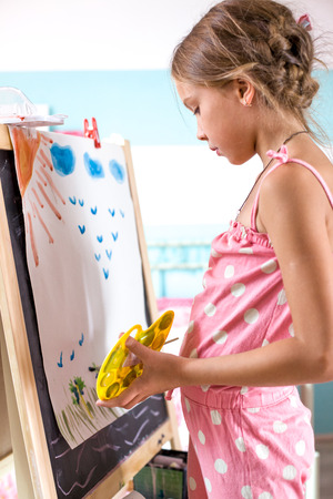 painter girl: 7-8 years old child drawing on easel in child room at home