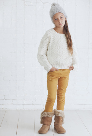 shoe model: Cute teenage girl 8-9 years old wearing knit trendy winter clothes posing over white brick wall Stock Photo