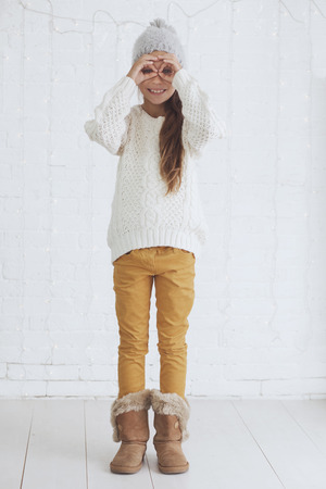 girl boots: Cute teenage girl 8-9 years old wearing knit trendy winter clothes posing over white brick wall Stock Photo