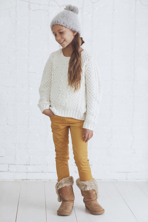 warm clothes: Cute teenage girl 8-9 years old wearing knit trendy winter clothes posing over white brick wall Stock Photo