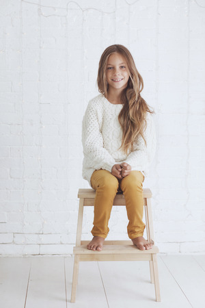 beautiful preteen girl: Cute little girl 8-9 years old wearing knit trendy winter clothes posing over white brick wall
