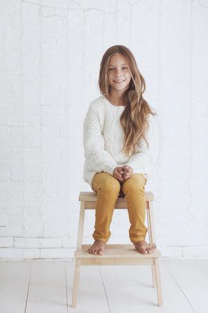 Niña linda 8-9 años de edad vestido tejer ropa de moda de invierno posando en la pared de ladrillo blanco