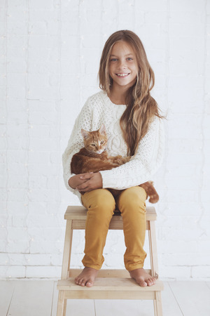 Cute teenage girl 8-9 years old wearing knit trendy winter clothes holding her ginger cat posing over white brick wall Stock Photo