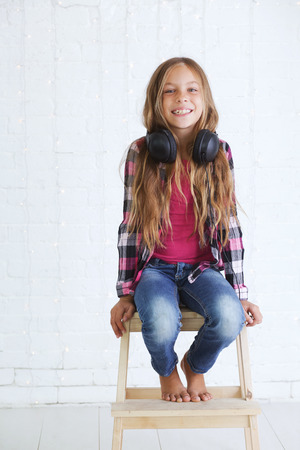 preteen: 8-9 years old stylish teen girl with black headphones posing on white background Stock Photo