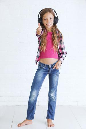 8-9 years old stylish teen girl with black headphones posing on white background photo
