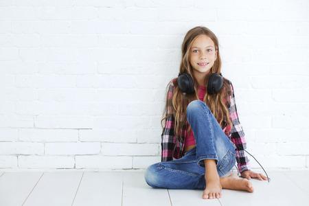 8-9 jaar oude stijlvolle tiener meisje met zwarte hoofdtelefoons die zich voordeed op een witte achtergrond Stockfoto