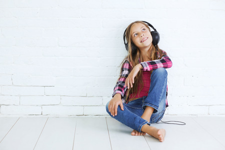 8-9 years old stylish teen girl with black headphones posing on white background Stock Photo