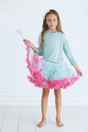 teenage girl dress: Studio portrait of cute little princess girl wearing holiday candy tutu skirt holding magic wand Stock Photo