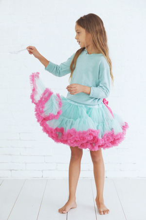 Studio portrait of cute little princess girl wearing holiday candy tutu skirt holding magic wand photo
