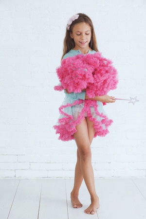 Studio portrait of cute little princess girl wearing holiday candy tutu skirt holding magic wand photo